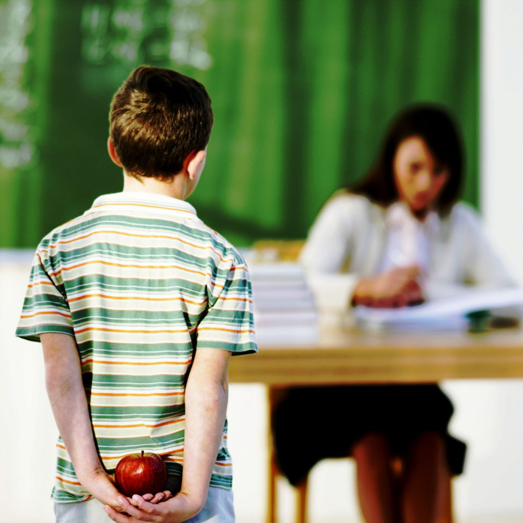 Boy (8-9) holding apple behind back, looking at teacher in classroom, focus on boy